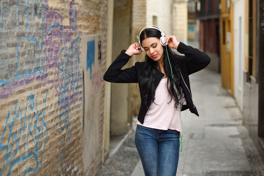 Woman in urban background listening to music with headphones