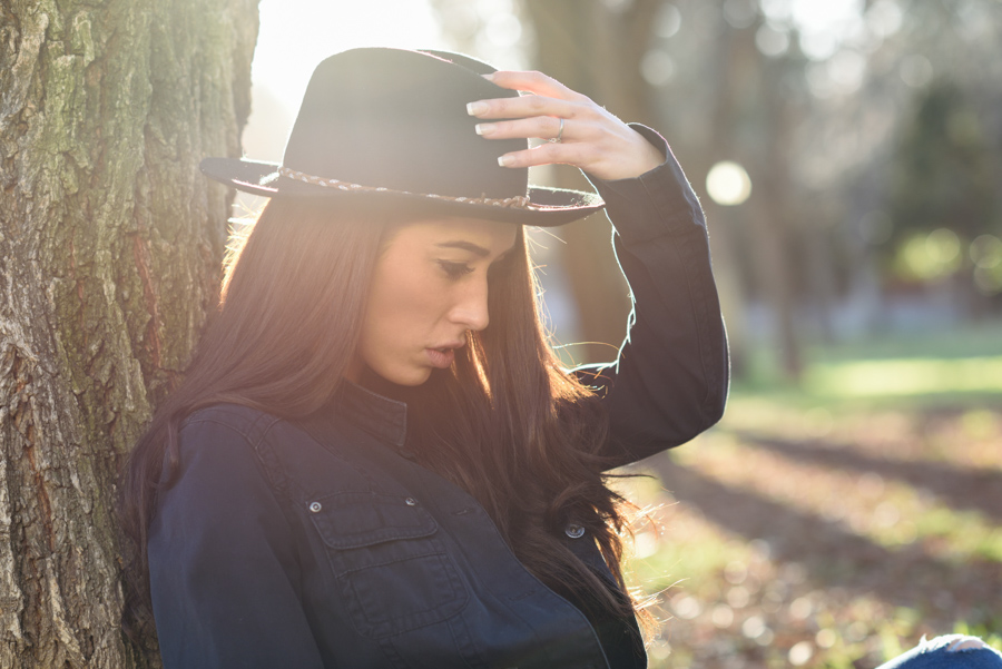 Portrait of thoughtful woman sitting alone outdoors wearing hat. Nice backlit with sunlight