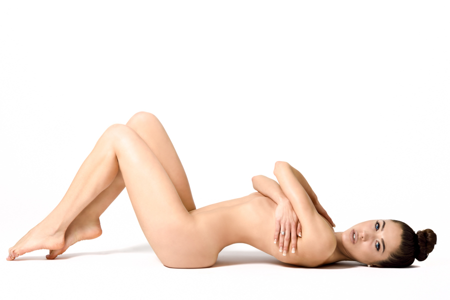 Young fit naked woman with healthy clean skin lying down, isolated on white