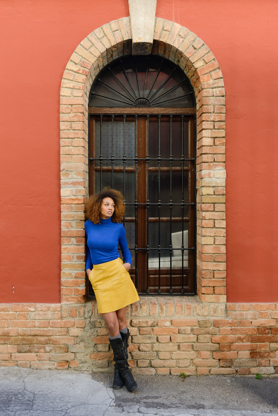Beautiful young African American woman, model of fashion, with afro hairstyle and green eyes wearing blue sweater and yellow skirt in urban background