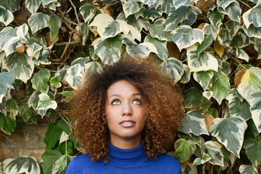 Beautiful young African American woman, model of fashion, with afro hairstyle and green eyes wearing blue sweater against leaves wall