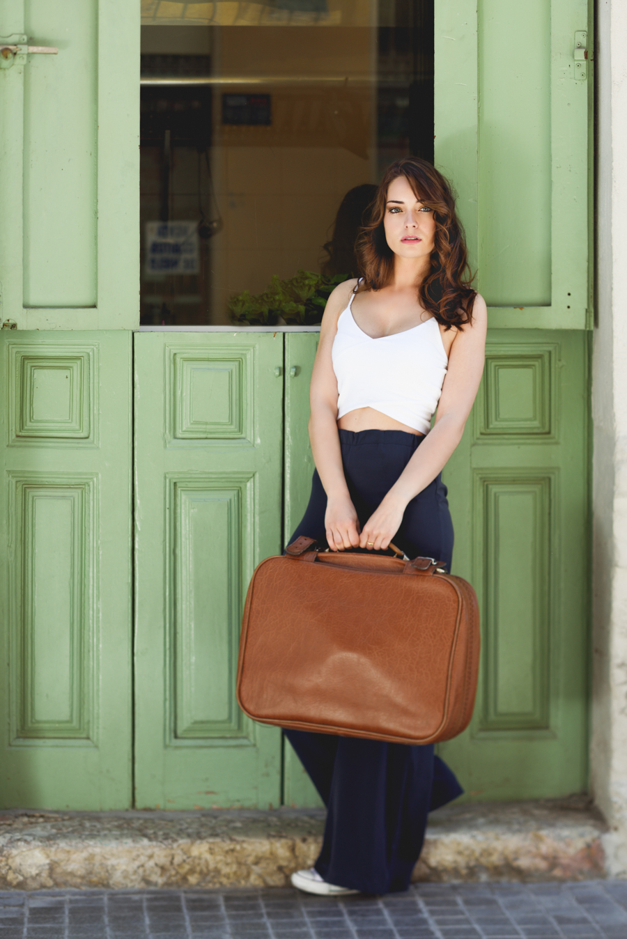 Beautiful girl with vintage bag against green door in urban background. Casual spring clothes