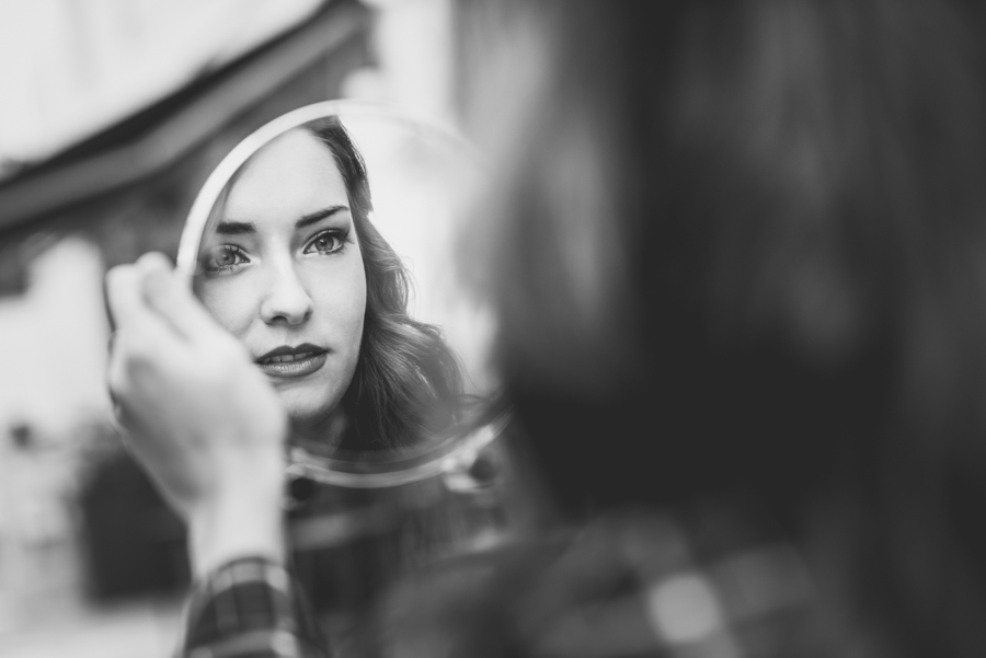 Portrait of young woman looking at herself in a little mirror in urban background. Black and white photograph.