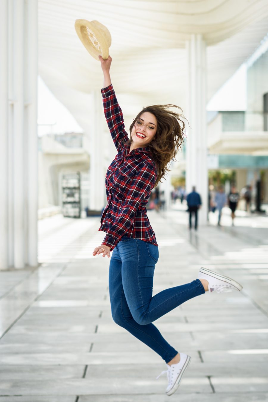 Young woman with beautiful blue eyes wearing plaid shirt and sun hat. Girl jumping in urban background.