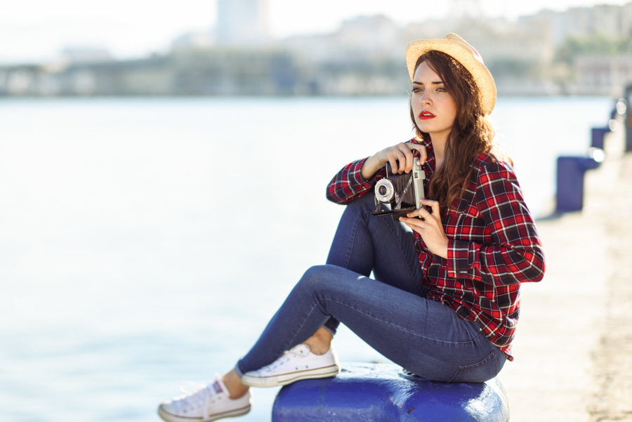 Young woman taking photographs with a vintage camera sitting in a harbour. Girl wearing plaid shirt, blue jeans and sun hat.