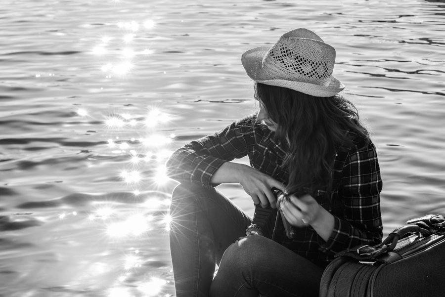 Young woman taking photographs with a vintage camera sitting in a harbour. Girl wearing plaid shirt, blue jeans and sun hat. Black and white photograph.