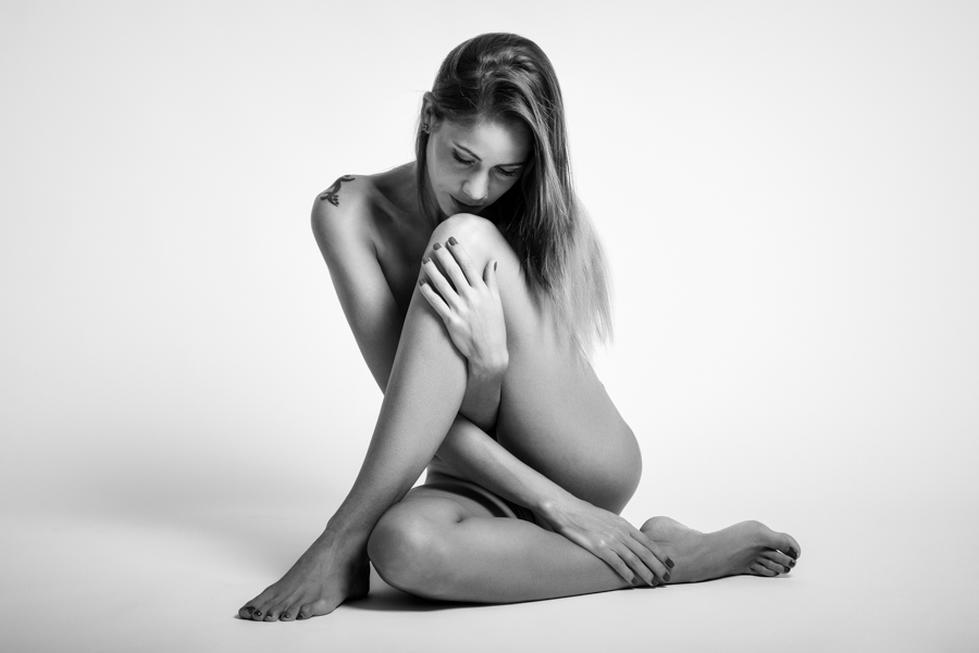 Young naked woman sitting on white floor. Perfect skin. Black and white photograph