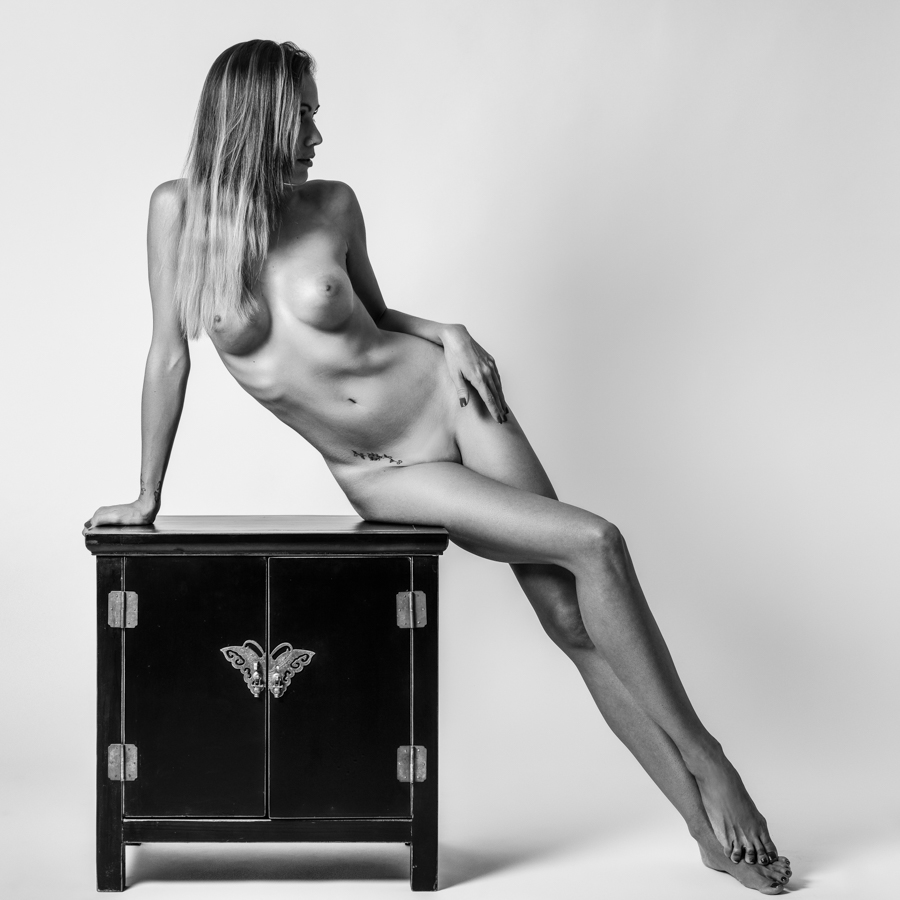 Young naked woman sitting on little table. Perfect skin. Black and white photograph