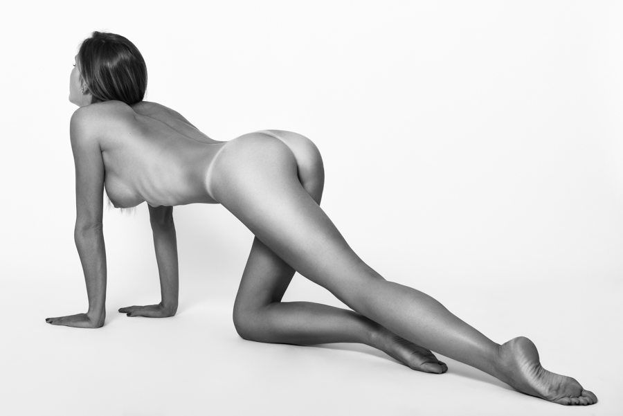 Young naked woman laying on white floor. Perfect skin. Black and white photograph