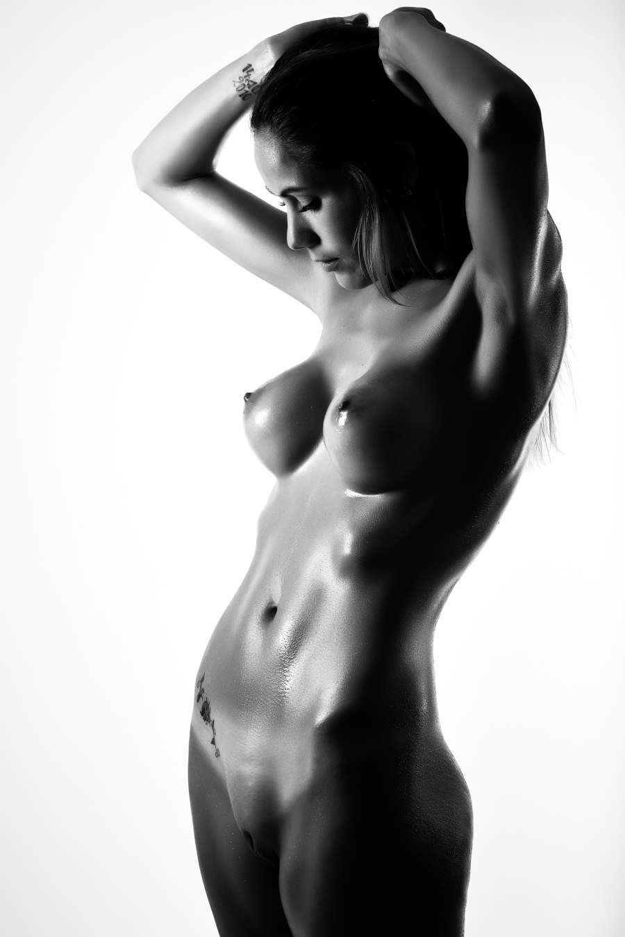 Young naked woman standing against white background. Perfect skin. Black and white photograph
