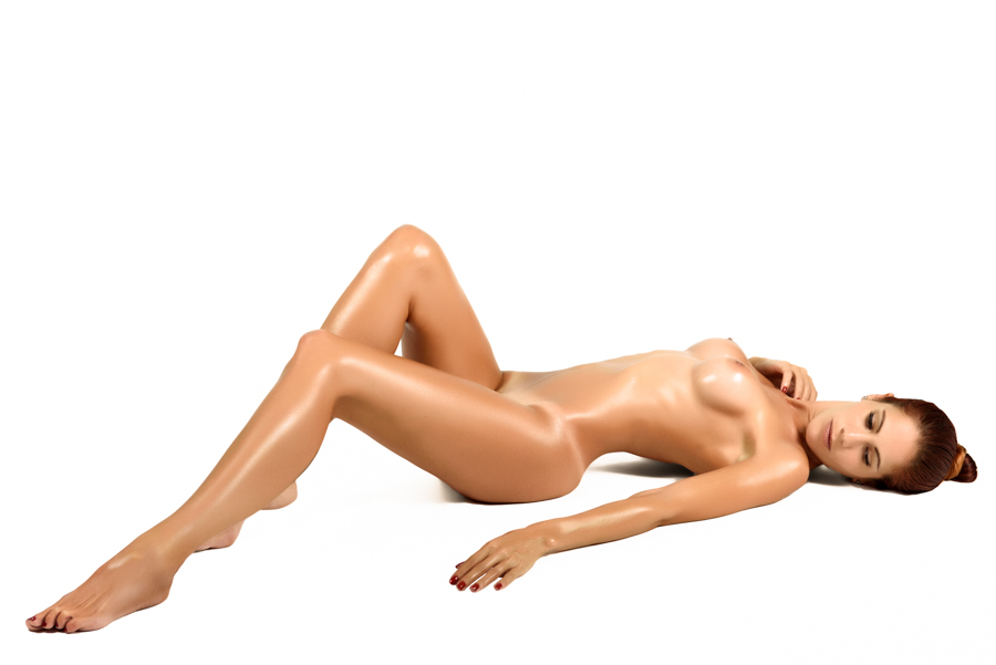 Young naked woman laying on white floor. Perfect epilated skin