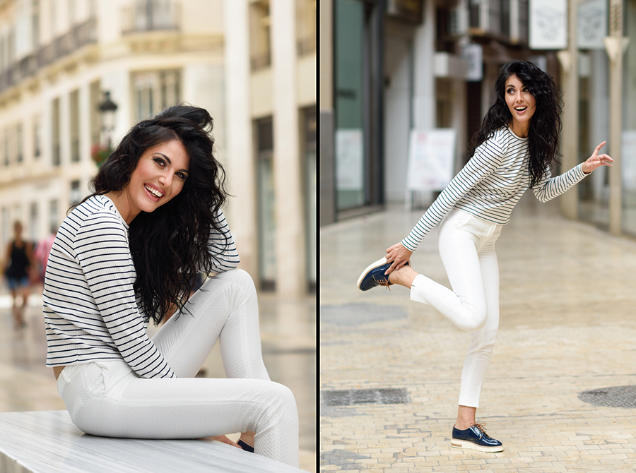 Brunette woman, model of fashion, wearing casual white clothes smiling in the street. Young girl with curly hairstyle sitting in urban background.